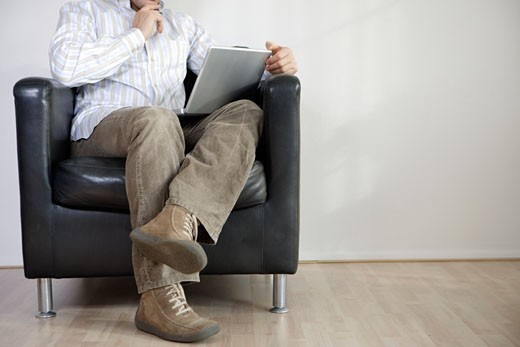 Stock Photo: 1779R-8340 Man using laptop in armchair
