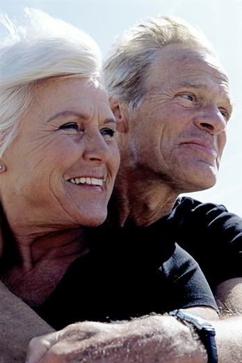 Senior couple hugging in wind : Stock Photo