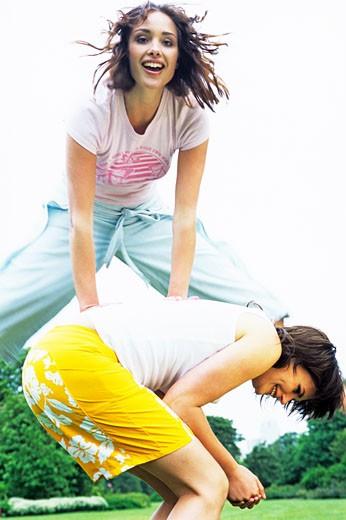 Women playing leapfrog : Stock Photo