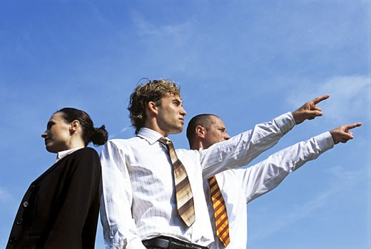 Businesswoman standing with two pointing businessmen : Stock Photo