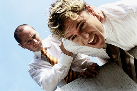 Businessman pushing co-worker over ledge : Stock Photo