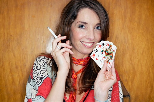 Stock Photo: 1779R-8908 Woman smoking and holding playing cards