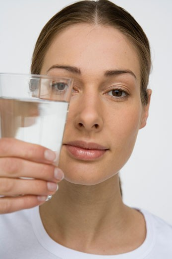 Woman holding out glass of water : Stock Photo