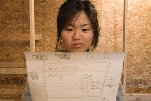 Close-up of teenage girl looking at blueprints : Stock Photo