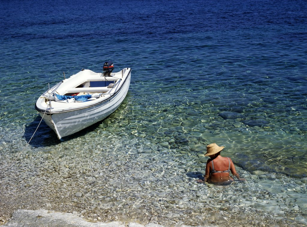 Stock Photo: 1783-10898 Woman wading in water next to boat, Corfu, North East Coast, Corfu, Greece