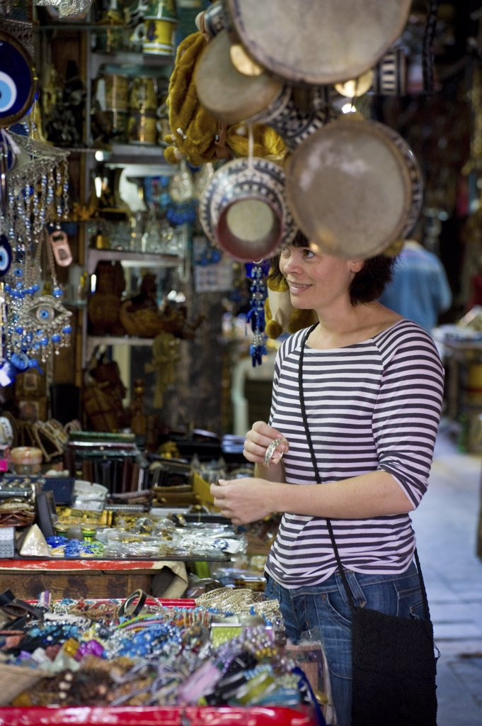 Stock Photo: 1783-11580 Female tourist buying souvenirs on souk, Cairo, Egypt.