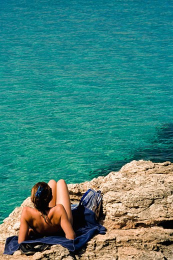 Woman sunbathing at Blue Lagoon, Comino, Malta : Stock Photo