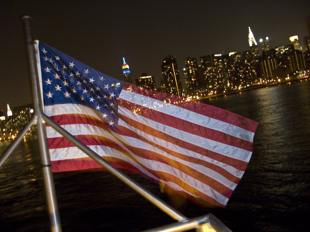 Stock Photo: 1783-24233 American flag in front of Manhattan skyline at night, New York City, New York State, USA.