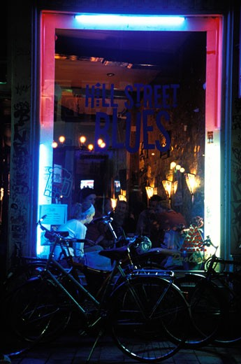 Hill Street Blues, trendy young people eating in a cafe / bar, bicycles, window front, neon lights. : Stock Photo