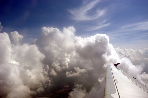Looking out over the wing of Air Jamaica plane whilst ascending through clouds. : Stock Photo