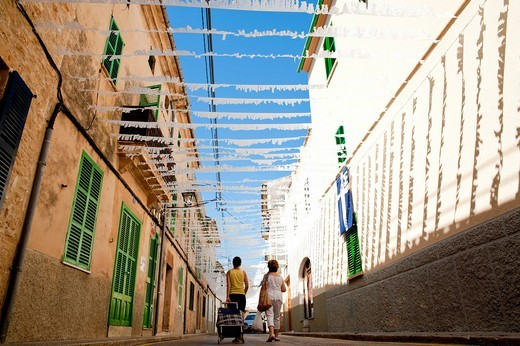 Women going shopping on a decorated streetAlcudia, Mallorca, Balearic Islands, Spain. Women going shopping on a decorated street : Stock Photo
