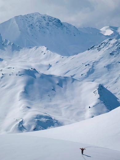 Lone snowboarder walks up snowy mountain to get fresh powder tracks.Les Arcs, France. Lone snowboarder walks up snowy mountain to get fresh powder tracks. : Stock Photo