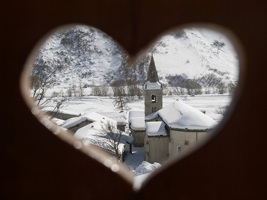 View through a heart shaped wooden balcony to the village church.Bonneval_sur_Arc, Val Cenis, Haute Maurienne, French Alps, Vanois National Park, France. View through a heart shaped wooden balcony to the village church. : Stock Photo