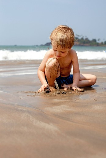 Stock Photo: 1783-31474 A boy on holiday plays with sand on Patnum beachPatnum beach, Goa, India. A boy on holiday plays with sand on Patnum beach
