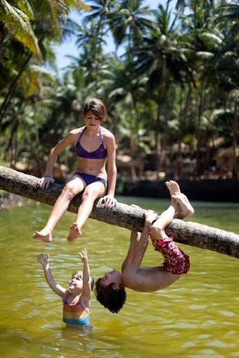 Kids play on a fallen palm tree trunk in the fresh waters of the lagoon on Cola beachCola beach, Goa, India. Kids play on a fallen palm tree trunk in the fresh waters of the lagoon on Cola beach : Stock Photo