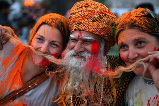 Stock Photo: 1783-31520 Cloured Dye On Female Tourists Who Pose With Rajasthani Guy With Long Beard At Elephant Festival,, Jaipur,Rajasthan State, India. Asia. Cloured Dye On Female Tourists Who Pose With Rajasthani Guy With Long Beard At Elephant Festival,