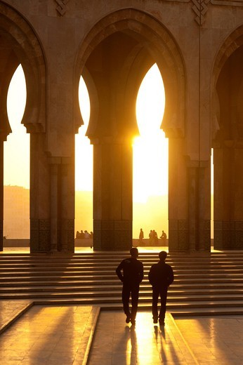 Two men walking through courtyard in front of the Hassan II mosque at duskCasablanca, Morocco. Two men walking through courtyard in front of the Hassan II mosque at dusk : Stock Photo