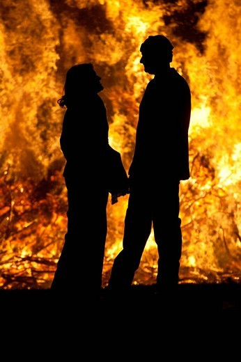 Silhouette of man and woman in front of large bonfire at Battle Bonfire nightEast Sussex, England. Silhouette of man and woman in front of large bonfire at Battle Bonfire night : Stock Photo
