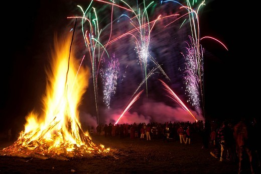 Stock Photo: 1783-31940 Crowd watching fireworks display beside large bonfire on Bonfire NightBattle, East Sussex, England. Crowd watching fireworks display beside large bonfire on Bonfire Night