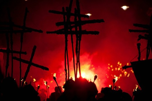 Silhouettes of 17 crosses lit by red flares on the United Grand ProcessionLewes, East Sussex, England. Seventeen crosses are carried to commemorate the 17 protestant martyrs killed on Lewes Hight Street between 1555 and 1557. Silhouettes of 17 crosses lit by red flares on the United Grand Procession : Stock Photo