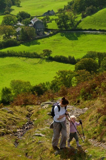 Mother leading child up path near Little LangdaleLake District National Park, Cumbria, England. Mother leading child up path near Little Langdale : Stock Photo