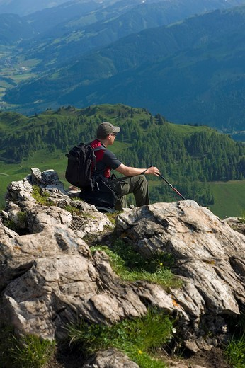 A male hiker enjoys the panoramic view from the Kitzbuheler Horn. Kitzbuehel, Tyrol, Austria. A male hiker enjoys the panoramic view from the Kitzbuheler Horn. : Stock Photo