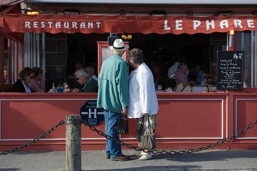 An Older Couple Looking At The Menu Outside A Restaurant In Cancale, Cancale. Brittany. France. An Older Couple Looking At The Menu Outside A Restaurant In Cancale : Stock Photo