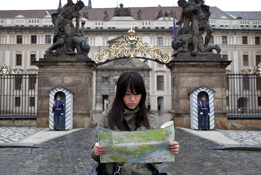 Stock Photo: 1783-32148 Young woman studying map outside Prague CastlePrague, Czech Republic, Europe. Young woman studying map outside Prague Castle