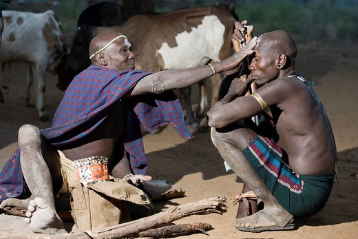 Stock Photo: 1783-32225 Olibuyzer Olibui, The Deputy Of The Priest Of The Northern Mursi Tribe In Charge Of Mapping The Future Through Dreams, Blessing A Young Man At Dawn Before Leaving To Tender The Cattle. , Maridungka Village / Mursiland / South Omo / Southern Nations, Natio. Olibuyzer Olibui, The Deputy Of The Priest Of The Northern Mursi Tribe In Charge Of Mapping The Future Through Dreams, Blessing A Young Man At Dawn Before Leaving To Tender The Cattle.
