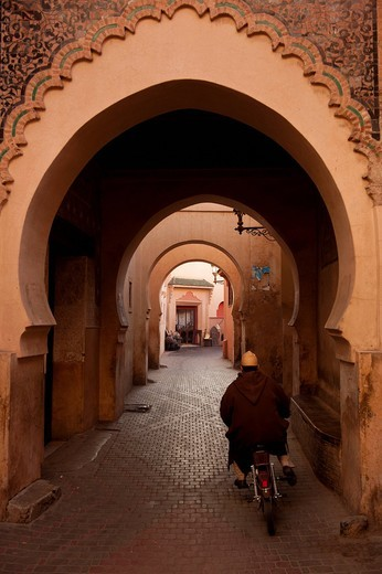 Man on moped going through arches in alleyway in the Medina of MarrakeshMarrakesh, Morocco. Man on moped going through arches in alleyway in the Medina of Marrakesh : Stock Photo