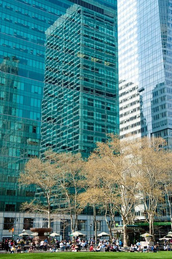 Skyscrapers Surrounding Bryant Park And People Enjoying The Sun, Garment District, Manhattan, New York, USA. Skyscrapers Surrounding Bryant Park And People Enjoying The Sun : Stock Photo