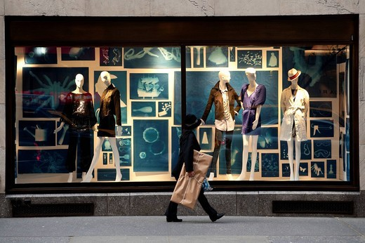 Woman Passing By A Designer Shop In 5Th Avenue, Midtown Manhattan, New York, USA. Woman Passing By A Designer Shop In 5Th Avenue : Stock Photo