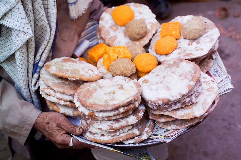 Stock Photo: 1783-36299 Person Carrying Tray With Baked Offering Food,Mid Section,Close Up, Nadhwara,Rajasthan,India