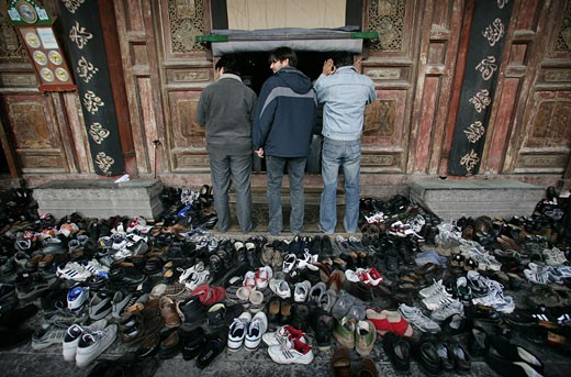 Hundreds of pairs of shoes lie outside the prayer hall during Friday prayers at the Great Mosque, Xian, Xi'an, Capital of Shaanxi Province, China  : Stock Photo
