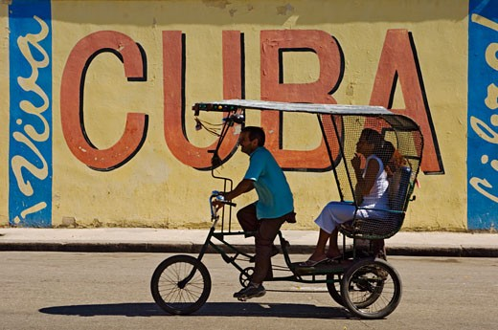 Stock Photo: 1783-3982 A Ricksaw passes a Viva Cuba sign, Havana, Cuba