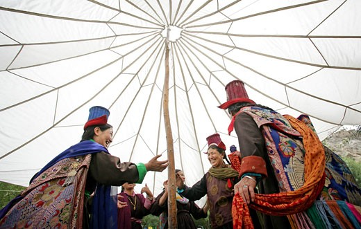 Ladakhi women in traditional dress and hats dancing under a traditional marquee, Leh, Ladakh, Indian Himalayas, India : Stock Photo