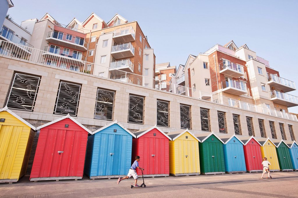 Colorful beach huts and modern apartments at Honeycombe Beach next to Boscombe Pier in Boscombe; Bournemouth, Dorset, England, UK : Stock Photo