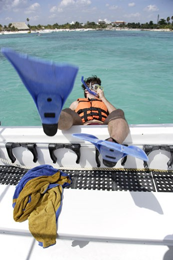Stock Photo: 1783-5083 Man wearing snorkel gear jumping boat on Mayan Riviera, Yucatan Peninsular,Quintana Roo State,Mexico