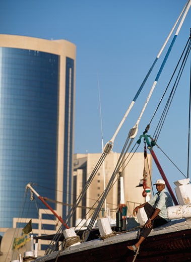 Man sitting on the bow of his dhow ,  The Creek, Dubai, UAE : Stock Photo