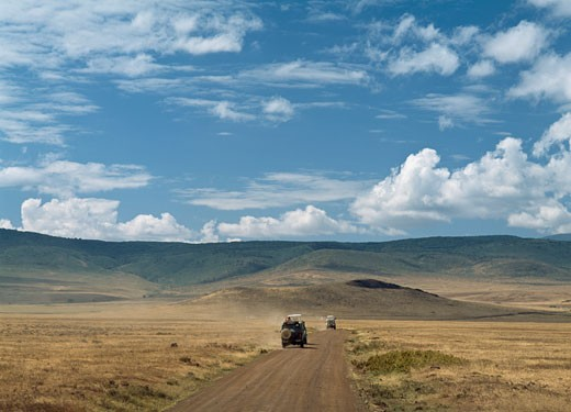 Jeeps travelling along dirt track,  Ngorogoro Crater National Park, Tanzania : Stock Photo