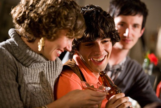 Young friends hanging out and drinking at bar together : Stock Photo