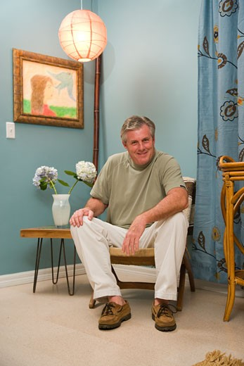 Stock Photo: 1785-10129 Middle-aged man sitting in living room