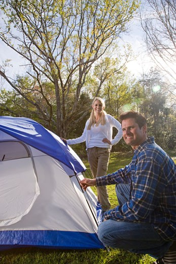 Portrait of couple pitching tent in park : Stock Photo