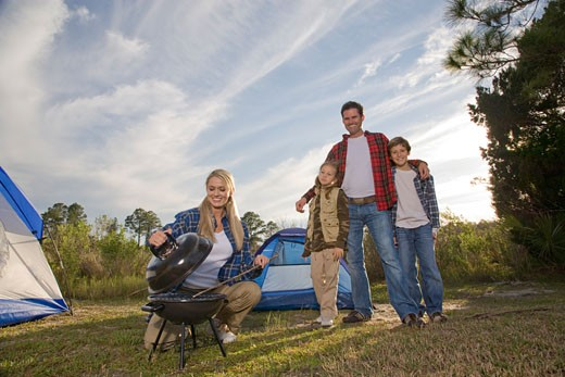 Young happy family by tent, woman preparing food on barbecue : Stock Photo