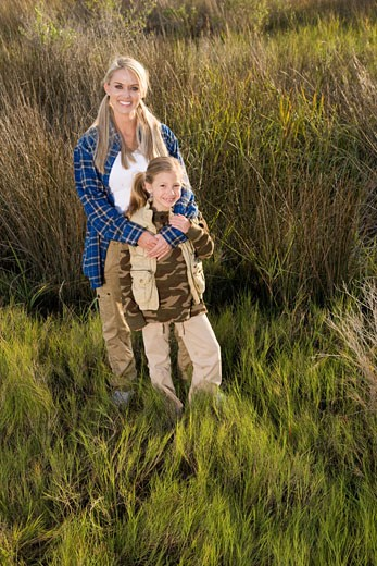 Portrait of mother and daughter standing in grass : Stock Photo