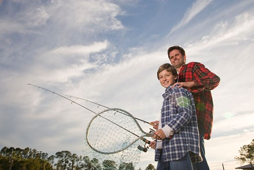 Happy son and father fishing, low angle view : Stock Photo