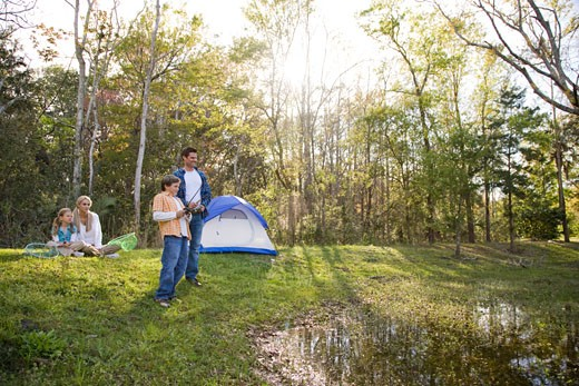 Family on camping trip fishing by tent : Stock Photo