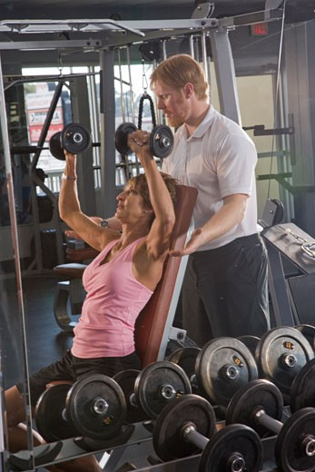 Middle-aged woman lifting weights at gym with personal trainer : Stock Photo
