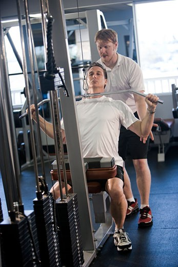 Middle-aged man lifting weights at gym with assistance from personal trainer : Stock Photo
