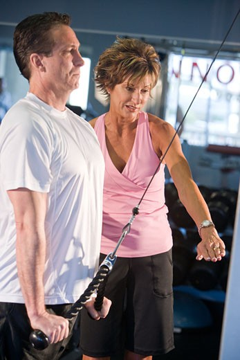 Middle-aged couple in workout clothes using weight machine at gym : Stock Photo